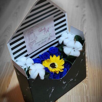 Aranjament Plic din flori parfumate de săpun, 9 trandafiri albaştri, 1 floarea soarelui şi 4 flori naturale de bumbac