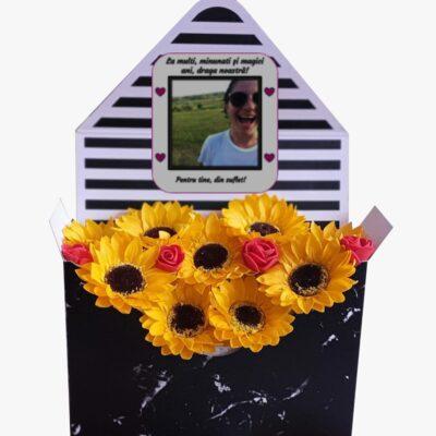 Aranjament personalizat din flori parfumate de săpun, 9 floarea soarelui şi 4 trandafiraşi sintetici în plic de carton